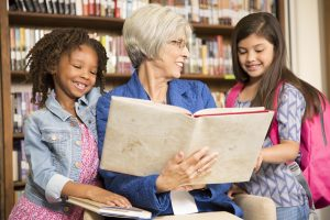 senior woman with glasses reads to two young girls