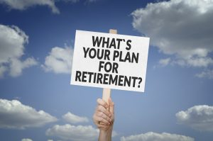 'What`s your plan for retirement?' sign held up with blue cloudy sky in background