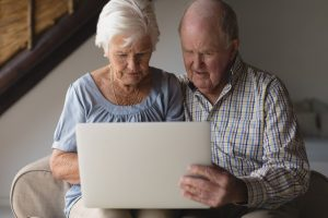 senior couple reviewing finances on laptop