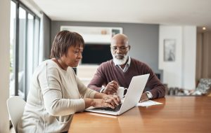 Cropped shot of a senior couple sitting together and using a laptop to work on their financial planning