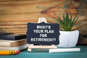 What's Your Plan for Retirement. small wooden board with chalk on the table.