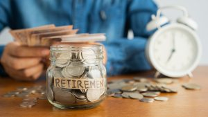 A coin in a glass bottle Image blurred background of business people sitting counting money and a retro white alarm clock, Investment business, retirement, finance and saving money for future concept.
