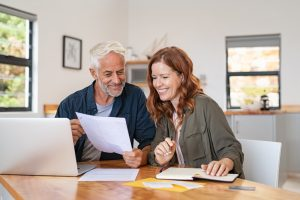 Mature smiling couple sitting and looking at laptop and paperwork for retirement planning.