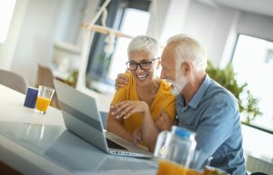 Closeup top view of a mid 60's couple sitting at a kitchen counter and looking at a laptop
